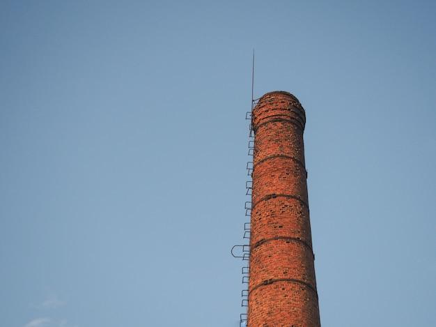 Baksteen rode industriële pijp op een achtergrond van blauwe hemel.