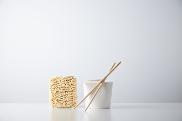 Baksteen van droge japanse noedels gepresenteerd in de buurt van gesloten blant afhaalmaaltijden doos met stokjes
