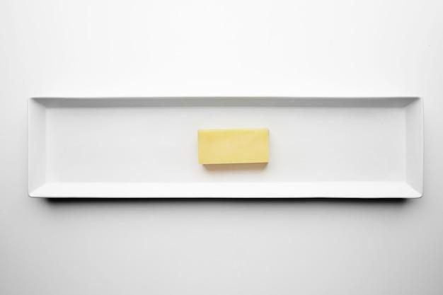 Baksteen van mozzarella kaas geïsoleerd op een witte plaat, bovenaanzicht. elke andere stevige kaas zonder gaten.