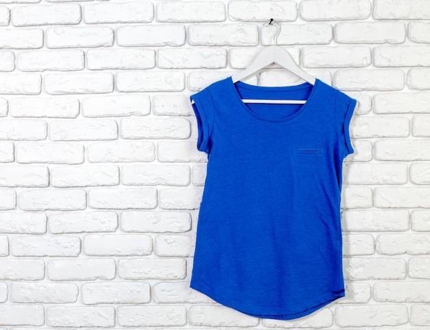 Baksteen witgekalkte muur met t-shirt op hanger