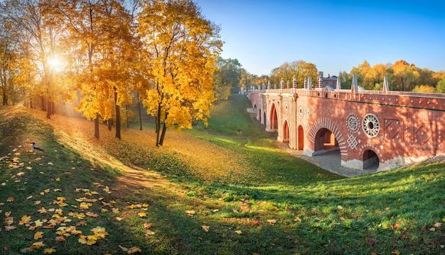 Bakstenen brug over een ravijn in het tsaritsyno-park in moskou tussen kleurrijke herfstbomen en bladeren op het gras in het licht van de ochtendzon