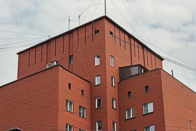 Bakstenen gebouw met meerdere verdiepingen en hemel met wolken