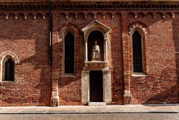 Bakstenen gevel in de middagzon van een religieuze veronese hermitage met een standbeeld van een heilige.
