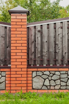 Bakstenen hek met houten overspanningen en grijs grind