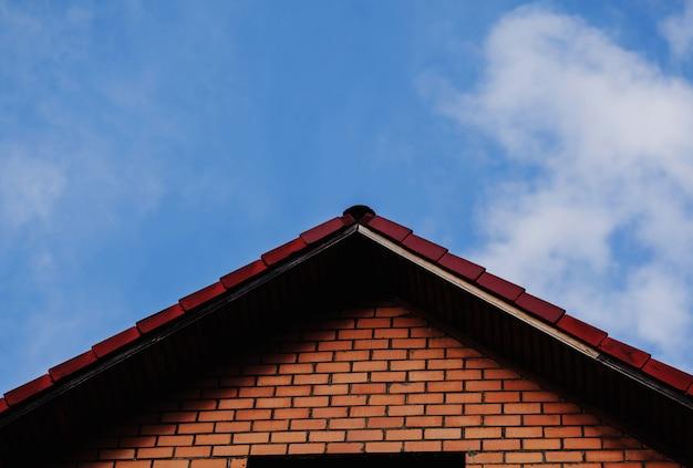 Bakstenen huis tegen een blauwe hemel. dak van een privéwoning