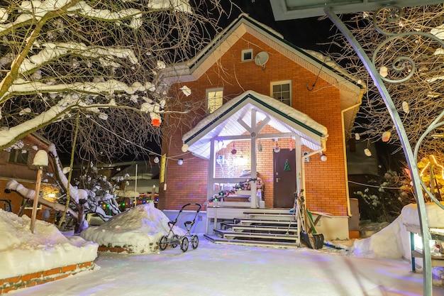 Bakstenen huisje in winterbos achtertuin kinderwagen bij het huis sneeuw op de paden van huis