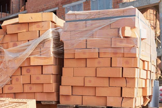 Bakstenen in pallets op een bouwwerf. bouwmaterialen. rode baksteen voor het bouwen van een huis.