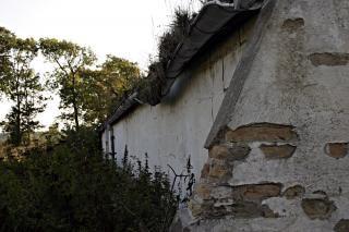 Bakstenen muur en een kapotte dakgoot