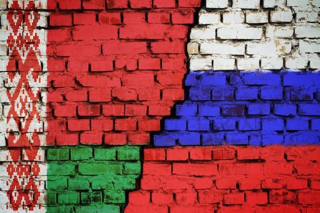 Bakstenen muur met een vlag van wit-rusland en rusland