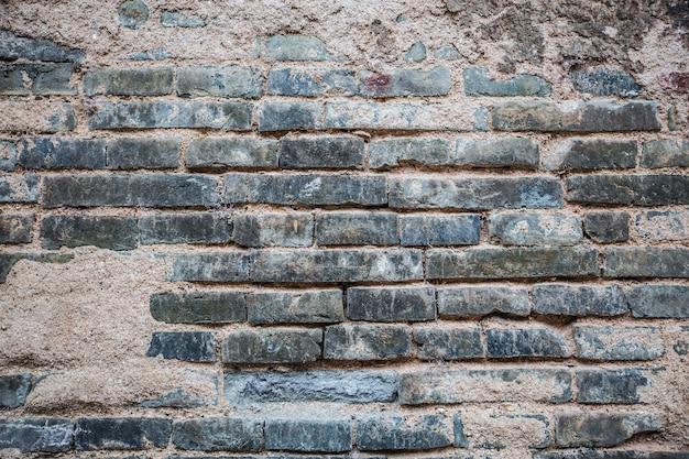 Bakstenen muur met gebroken cement