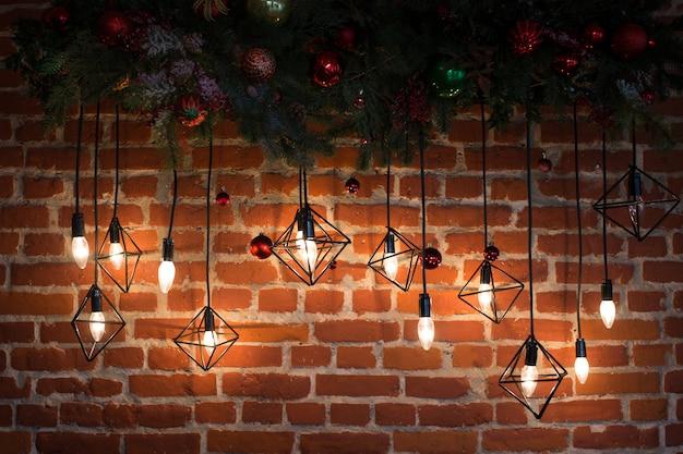 Bakstenen muur met gloeilampen en nieuwjaarsdecoratie