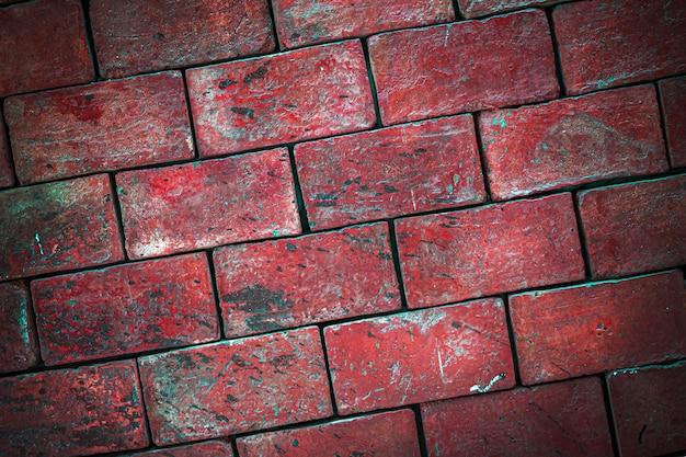 Bakstenen muur van rode blokken met een helling van metselwerk en een vignet.