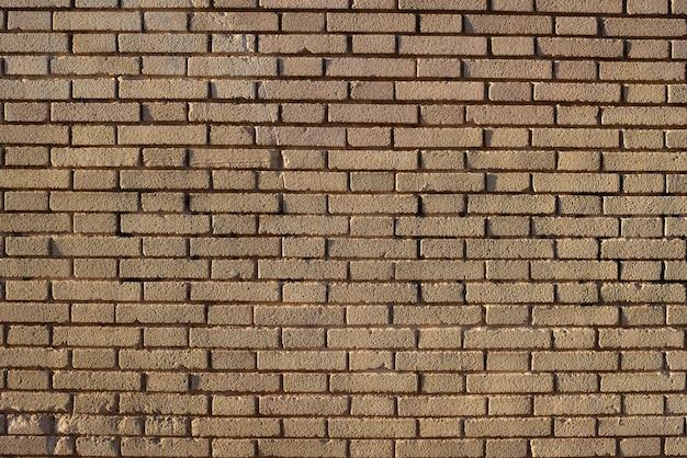 Bakstenen muurachtergrond bij zonsondergang met zonstralen, steentextuur.