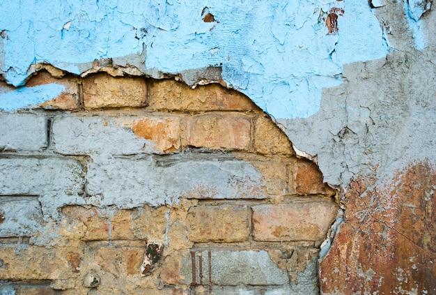 Bakstenen oude verweerde muur met gebarsten geverfd gips