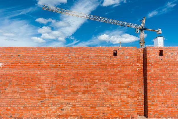 Bakstenen rode muur van een nieuw huis op de achtergrond van een kraan