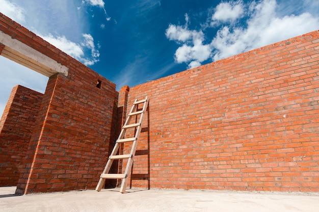 Bakstenen rode muur van een nieuw huis op een blauwe hemelachtergrond