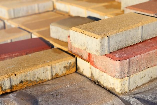 Bakstenen van bouwmaterialen liggen in afwachting van stoïcijns werk op straat