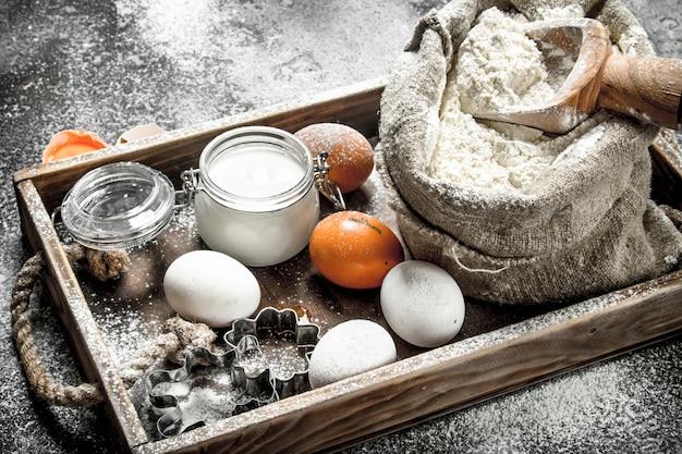 Baktafel. ingrediënten voor deeg in een houten dienblad. op een rustieke tafel.