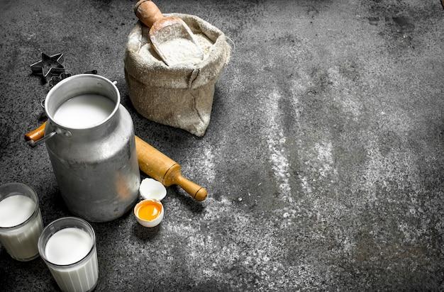 Baktafel. melk, bloem en andere ingrediënten voor het deeg. op een rustieke tafel.