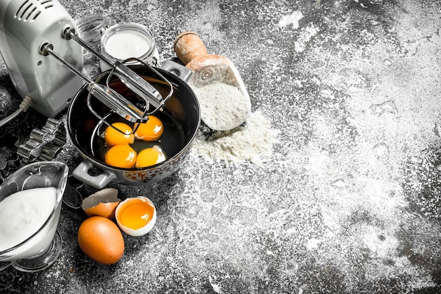 Baktafel. mix de eieren met een mixer om een deeg te maken. op een rustieke tafel.