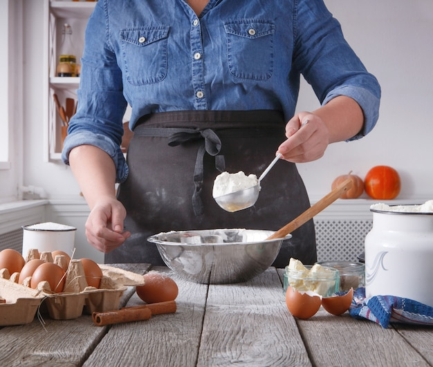 Bakvoorbereiding, deeg maken. doe er bloem in, kom op rustieke houten tafel, kook ingrediënten. vrouwelijke chef-kok bakker bij kooklessen