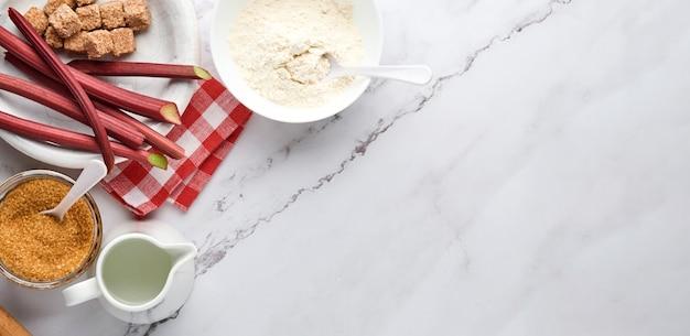 Bal deeg en ingrediënten bloem, water, boter, suiker en rabarber voor het bakken op witte marmeren achtergrond met afstoffen van bloem. recept stap voor stap. selectieve aandacht. bovenaanzicht. banier.