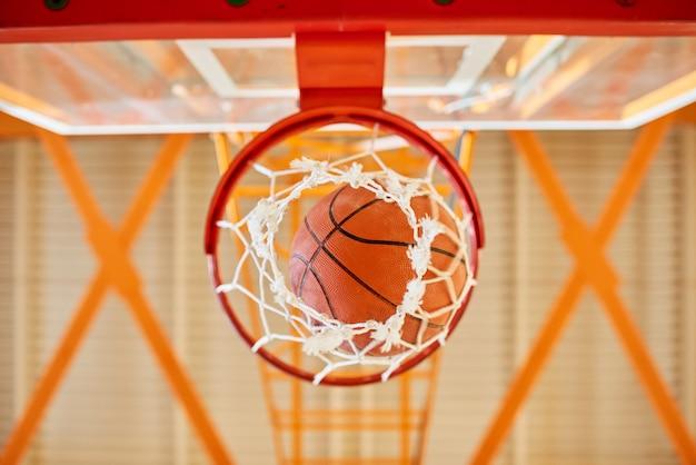 Bal die door basketbalmand valt