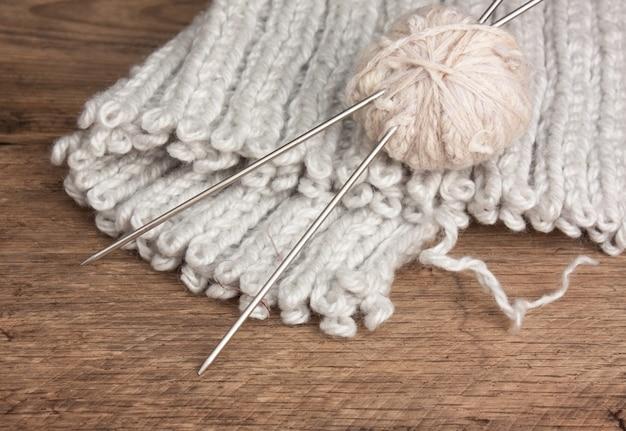 Bal van wol en breinaalden op een houten achtergrond