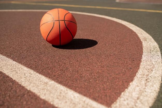Bal voor het spelen van basketbal liggend op sportveld of stadion tussen twee witte lijnen op zonnige dag