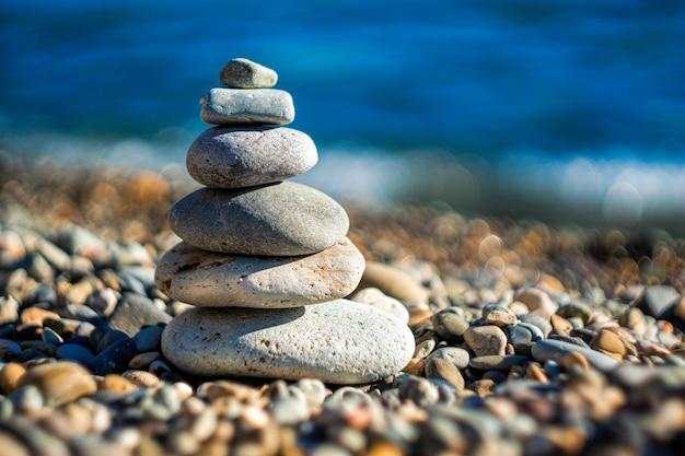 Balanced pebbles pyramid op het strand op zonnige dag en heldere hemel bij zonsondergang.