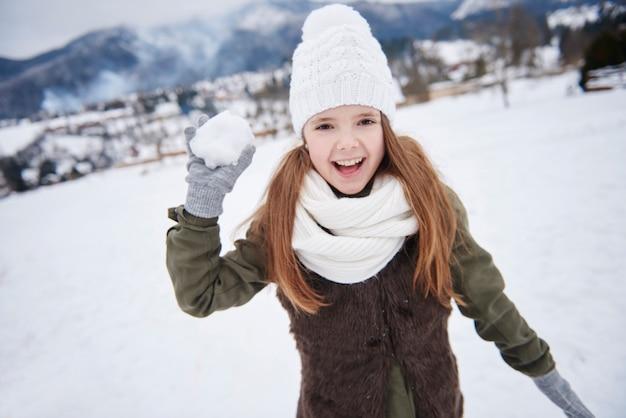 Baldadig meisje met in hand sneeuwbal