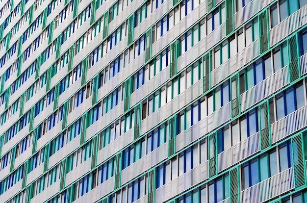 Balkons en ramen van een gebouw, appartement huizen getextureerde beige groene roosters.