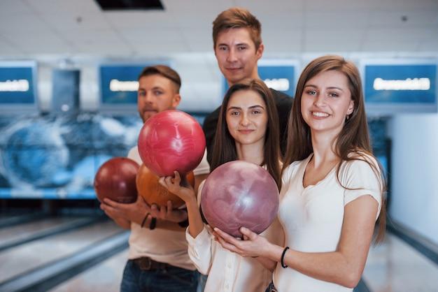 Ballen in handen houden. jonge vrolijke vrienden vermaken zich in het weekend in de bowlingclub