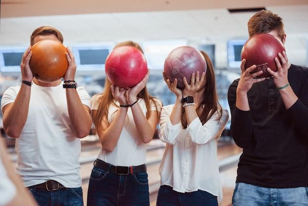 Ballen met verschillende nummers erop. jonge, vrolijke vrienden vermaken zich in het weekend in de bowlingclub