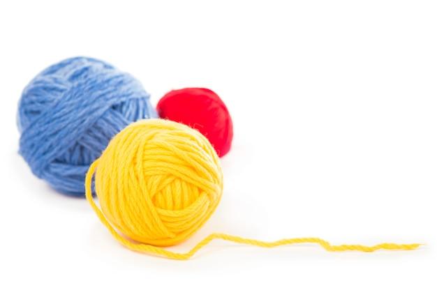 Ballen van blauwe, rode en gele wollen draden op de witte achtergrond