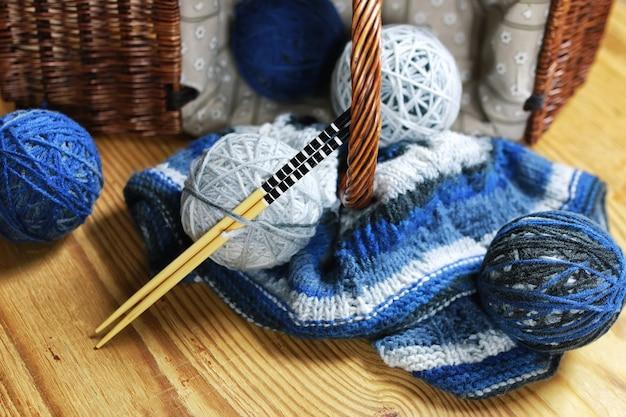 Ballen van wol en breinaalden op een houten ondergrond