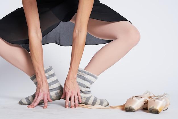 Ballerina benen in gestreepte sokken en pointe-schoenen op lichte achtergrond