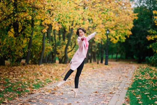 Ballerina dansen in de natuur tussen herfstbladeren in eerlijke vacht.