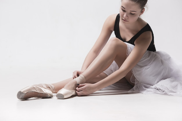 Ballerina danser gaan zitten met haar benen gekruist