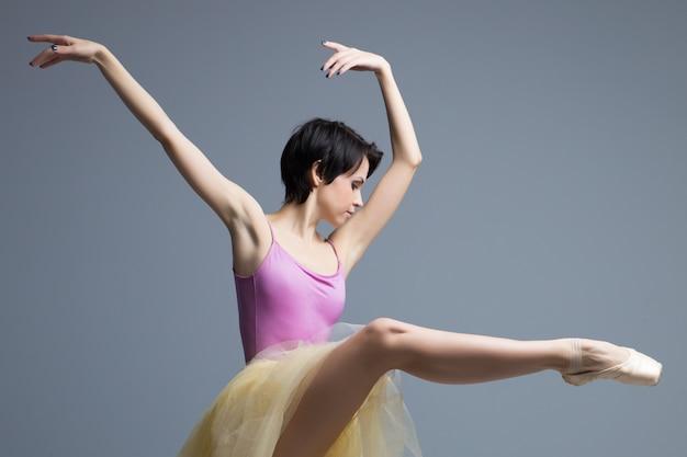 Ballerina danst in de studio op grijs