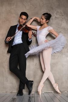 Ballerina die aan musicus luistert die viool speelt