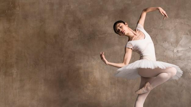 Ballerina die een tutu draagt die met exemplaarruimte danst