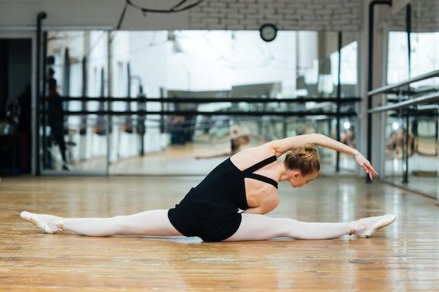 Ballerina doen rekoefeningen op de vloer in balletles