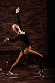 Ballerina in donkere bodysuit, in jurk in donker interieur studio. muur van bakstenen, piano. houten vloer.