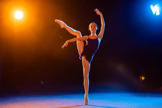 Ballerina in een zwarte jurk danst verlicht door veelkleurige stralen van schijnwerpers