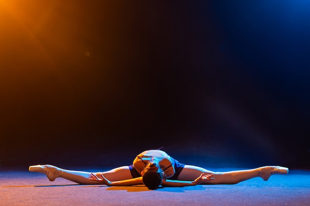Ballerina in een zwarte jurk ligt in een touw op een zwarte muur verlicht door veelkleurige stralen van schijnwerpers
