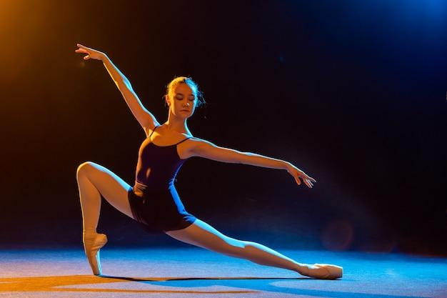 Ballerina in een zwarte jurk vormt op een zwarte muur verlicht door veelkleurige schijnwerpers.
