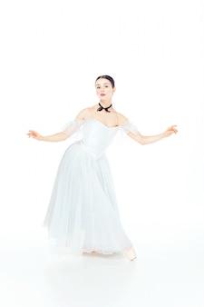 Ballerina in het witte kleding stellen op pointeschoenen, studiowit.
