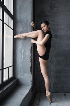 Ballerina in turnpakje poseren bij het raam