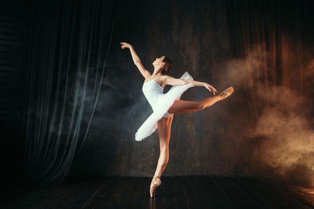 Ballerina in witte jurk dansen in balletles
